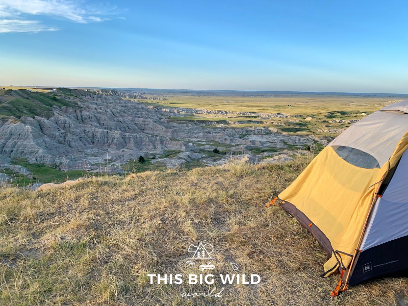 On the right hand side, a gray and yellow tent is setup on dry grass at the edge of a cliff overlooking the sweeping Badlands rock formations below. In the distance are RVs and other tents along the cliff. Below is green grass with bison roaming. The sun is coming into the frame from the left hand side.