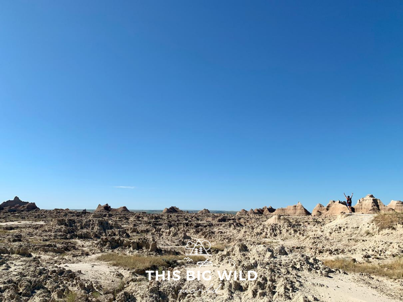 The lower third of the image shows jagged clay rock formations all the way to the horizon. The upper portion of the image is clear blue sky. On the right hand side, I am standing, looking very small standing on one of the rock formations with my hands raised over my head.