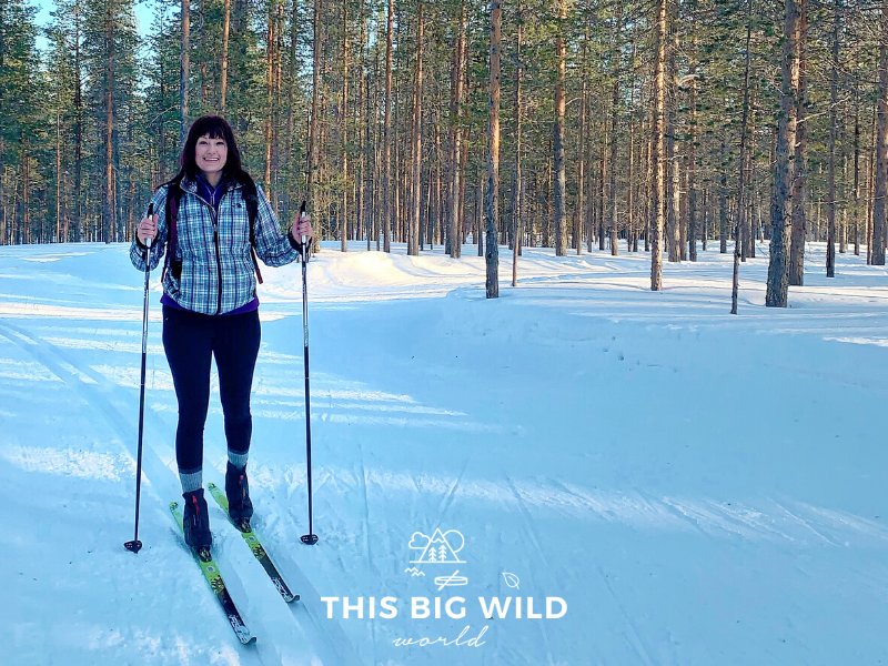 I, a woman, am wearing a plaid jacket and black leggings on cross-country skis with poles. I'm standing on a groomed cross-country ski path with snow covering the ground and a forest of pine trees behind me in Levi Finland.
