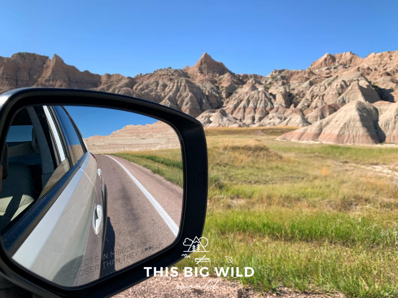 The left hand side of the photo is a closeup of a rear view mirror on a white vehicle, showing the open road and jagged rock formations in the reflection. The right hand side show the landscape on the road ahead, with colorful rock formations, green grass and a bright blue sky.