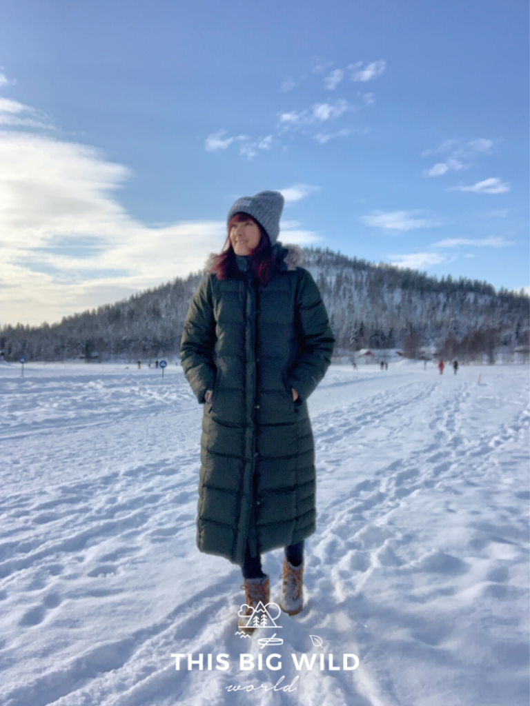 I, a woman, is bundled up in a puffy green ankle length coat and grey winter hat standing on snow on top of a frozen lake in Levi Finland. Behind me stands Katka Fell, a mountain that's popular for snowshoeing.