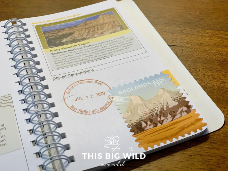 A close up page in my National Parks passport. On the top half of the page is the Rocky Mountain Region sticker, which is purchased at the park visitor center. One the lower half is a date stamped (July 12 2020) Badlands National Park stamp and an artistic sticker purchased in the visitor center.
