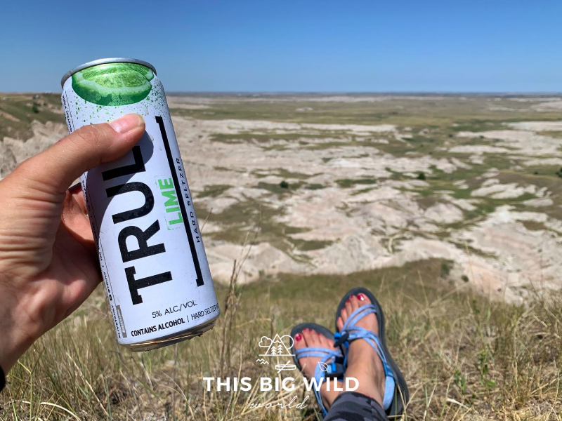 On the left side of the frame, my hand is holding a Truly lime hard seltzer can. At the bottom of the image you can see my feet stretched out in the grass with blue Chaco sandals. In the distance is a valley below with rocks formations, grassland and grazing buffalo.