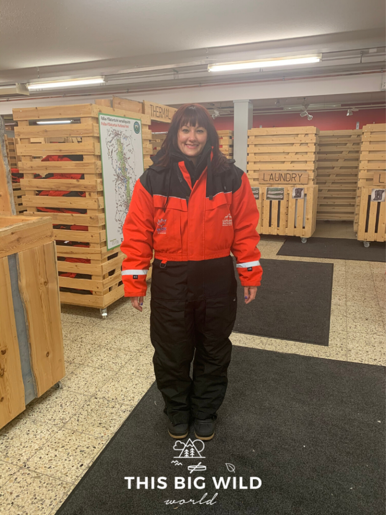Me standing wearing a puffy red and black jumpsuit and boots provided by Lapland Safaris before the nighttime snowmobile safari in Levi Finland. Behind me are wooden containers used to store the gear for the tours.