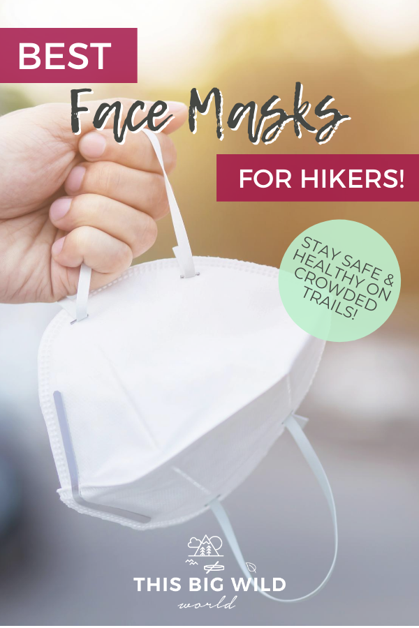 Text: Best Face Masks for Hikers! Stay safe & healthy on crowded trails. Image: A hand is on the left side of the frame, holding a white face mask by the ear loop. the background is blurred but green and a hint of sunshine from the top right corner.