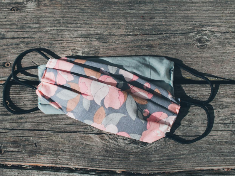 Two face masks rest on top of each on wooden planks. The masks have pink, green and gray floral design and black ear straps. The best face mask for hikers has 3 layers of fabric but is still breathable and comfortable.