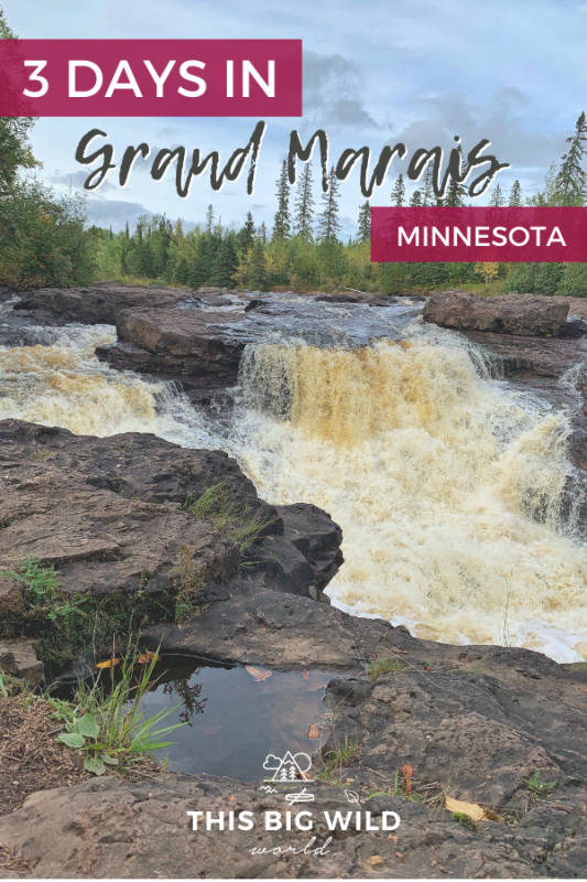 Text: 3 Days in Grand Marais Minnesota Background Image: Wide waterfalls flows over brownish red rocks with smaller waterfalls overflowing on either side. In the distance is a line of green and yellow trees with a bright blue sky overhead.