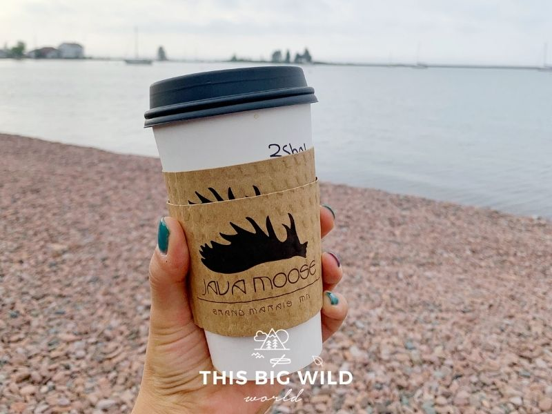 A woman's hand with teal nail polish holds a disposable cup of Java Moose coffee with a rocky shore and Lake Superior in the background.