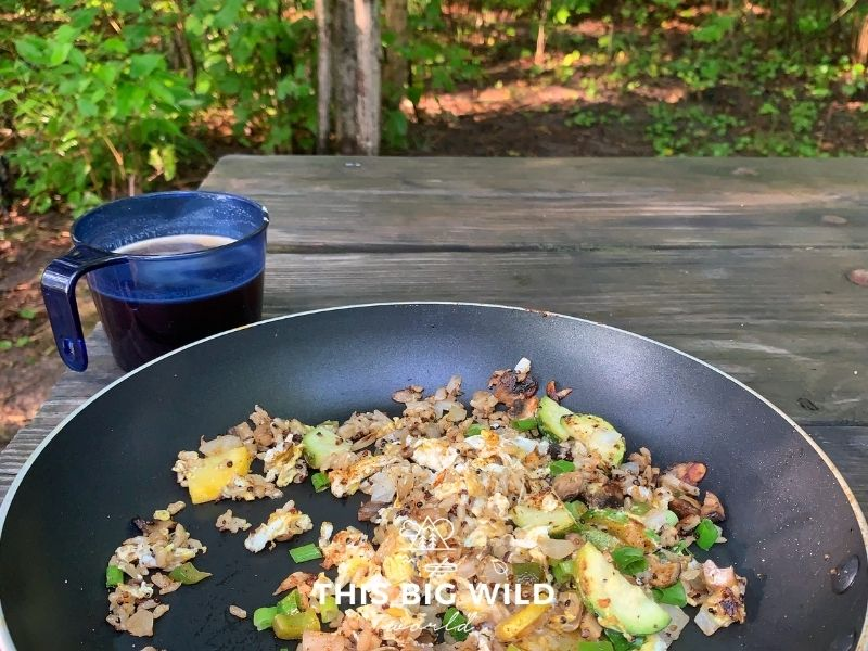 A skillet with eggs, quinoa, and vegetables sits on a wooden picnic table with a blue plastic mug filled with coffee. Green trees and forest are in the background.