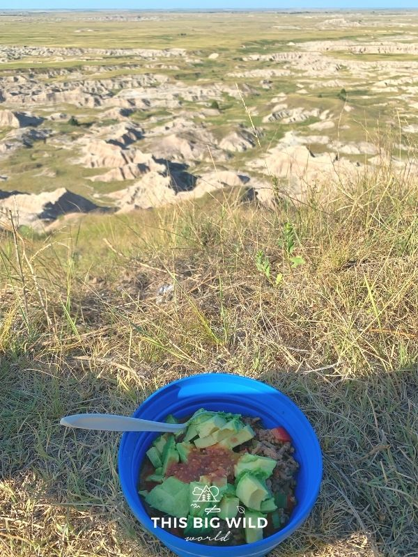 A blue Sea to Summit collapsible camping bowl is filled with a burrito bowl, topped with fresh avocado and salsa. The bowl is sitting in brown grass overlooking the Badlands.