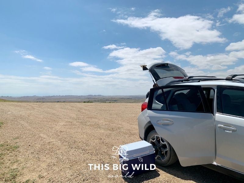 A gravel road overlooks green prairies. In the right foreground is a white SUV with a blue and white cooler sitting on the ground next to it.