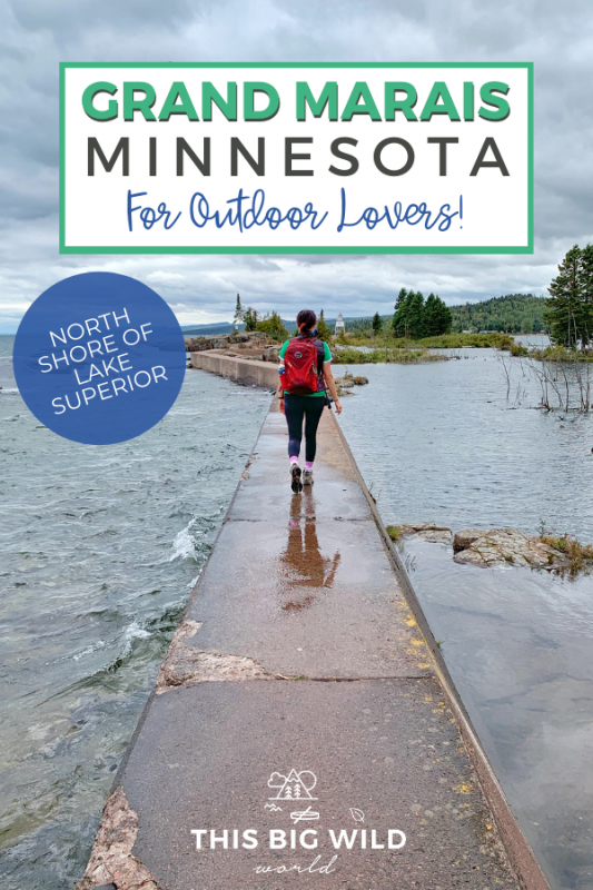 Text: Grand Marais Minnesota for Outdoor Lovers! Subtext: North shore of Lake Superior Background Image: A woman walks on a narrow concrete path with water from Lake Superior on either side. In the distance is a green forest a small white light house and a cloudy dark blue sky overhead.
