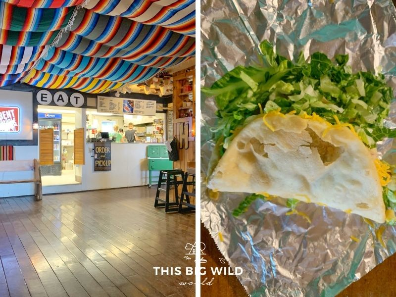 Left: Inside of Hungry Hippie Tacos there are wooden floors and colorful blankets draped from the ceiling. There's a small counter where you place your order. Right: An upclose picture of a frybread taco which looks like a deep fried taco shell folded in half with cheese and lettuce coming out of it sitting on a piece of aluminum foil.