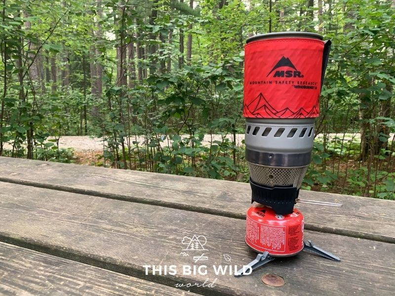 The MSR Windburner backpacking stove has a small red fuel canister, black and silver burner and an insulated red container that sits on top to boil water in. The stove is sitting on a wooden picnic table with green trees behind it.