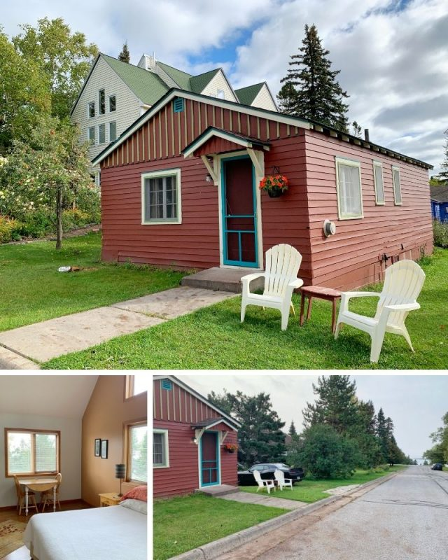 Top: Small red cabin with two white lawn chairs in the grass out front. A small pot of flowers hangs next to the bright blue screen door. Behind tall beige home, which is the bed and breakfast. Bottom left: A queen size bed with white duvet sits along a tall tan wall of windows looking out onto trees. A small two person table is against the wall to the left. Bottom right: The small red cabin is on the left. On the right is the street, which leads straight down to Lake Superior just blocks away.