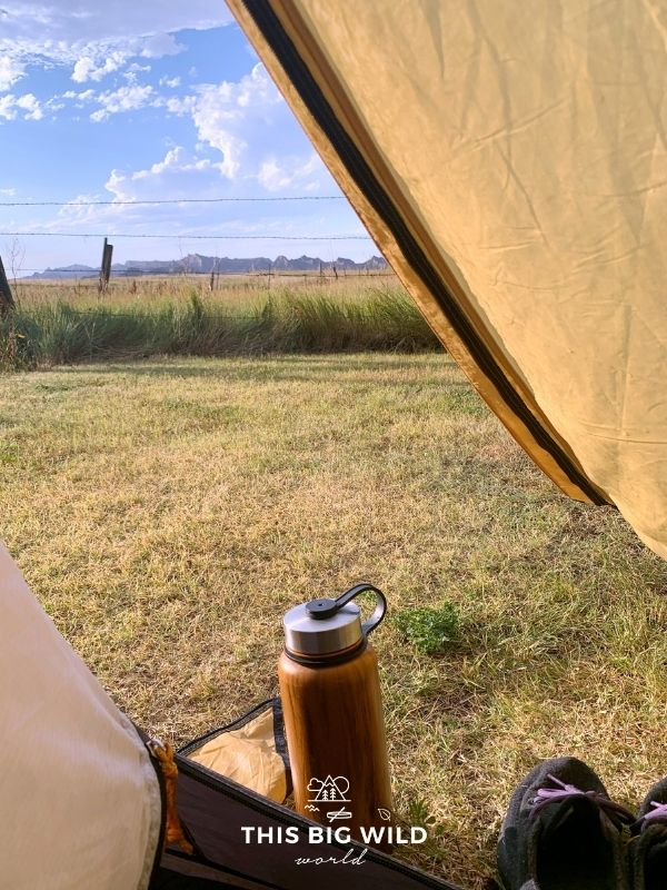 View from inside of a tent looking out towards a mountain range in the distance and blue skies overhead. Next to the tent is a wooden finished water bottle and sneakers sitting on the grass.