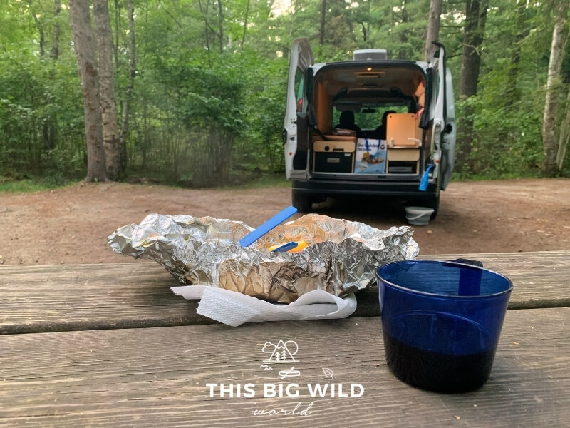 A foil packet dinner and blue plastic cup sits on a wooden picnic table in the foreground. In the background is the rear of the campervan open with lights on showing a small sink and refrigerator.
