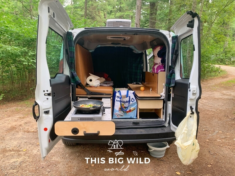 The rear doors of a campervan are open showing the countertop pulled out. Food is cooking in a skillet on a burner on the countertop. The bed is setup as a bench with cooking supplies sitting on it. The van is parked at a campsite in a forest.