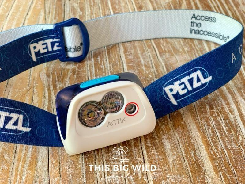 An up close shot of a blue and white headlamp laying on a wooden surface. The band is blue on the outside with the Petzl logo and white on the inside. The lamp itself is white with a blue button and three different bulbs.