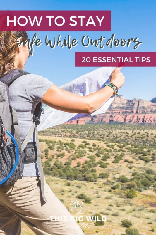 Text: How to Stay Safe While Outdoors - 20 Essential Tips Image: Women with her back to the camera on the left side of the frame wearing a backpack and holding a map. Behind her is a desert scene with green brush and mountains in the distance.