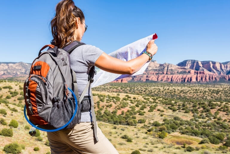 A woman is hiking in desert area with mountains in the distance. Her back is turned to the camera. She's wearing a backpack and looking at a map.