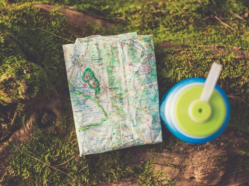 A paper trail map is folded and faded laying on a green mossy surface next to a blue and lime green water bottle.