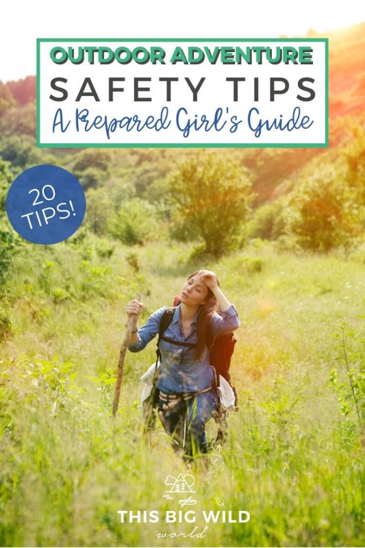 Text: Outdoor Adventure Safety Tips - A Prepared Girl's Guide. 20 Tips! Image: A woman walks through tall grass wearing a backpack and carrying a walking stick. Behind her is a large hill and in the sun setting in the top right of the frame.