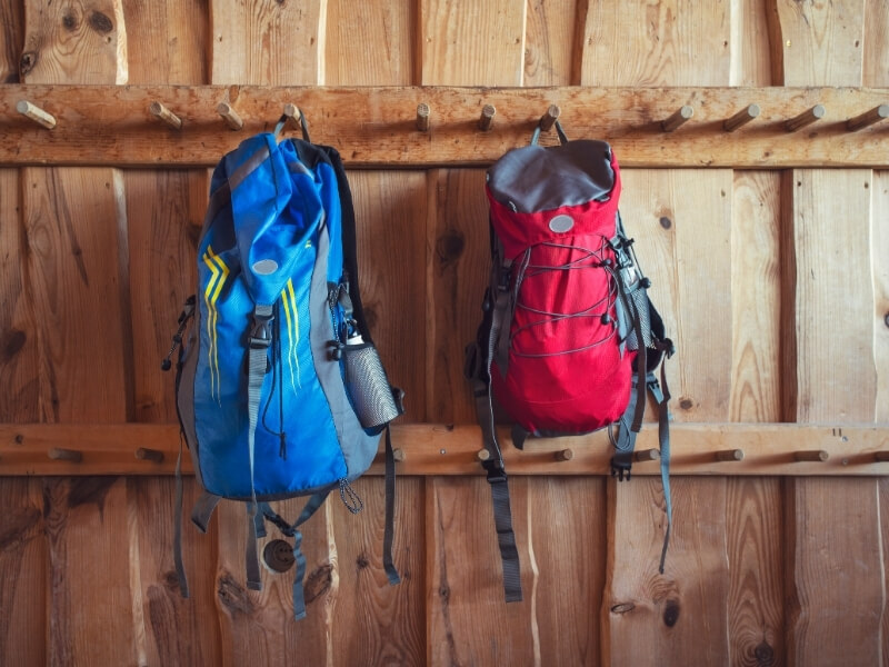 A wood paneled wall has two rows of wooden rungs hanging horizontally. On two of the rungs there are backpacks hanging. On the left is a blue backpack and on the right is a red backpack.