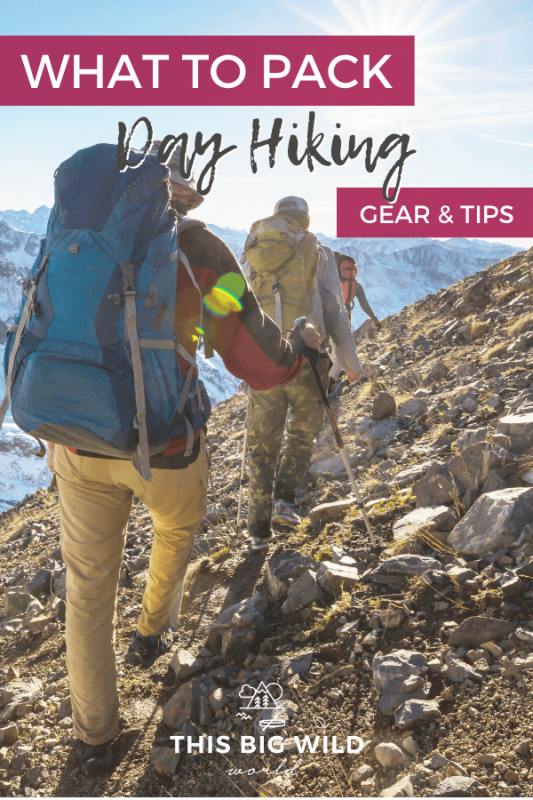Text: What to Pack Day Hiking Gear & Tips Image: 3 adults walking away from the camera on a slanted rocky trail with a snow covered mountain in the distance.