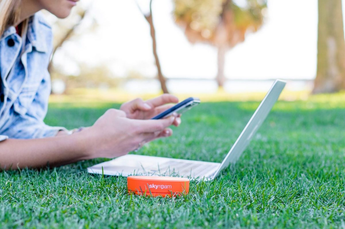 A round orange Skyroam portable wifi device sits in the grass next to a person laying in the grass working on the laptop and cell phone.
