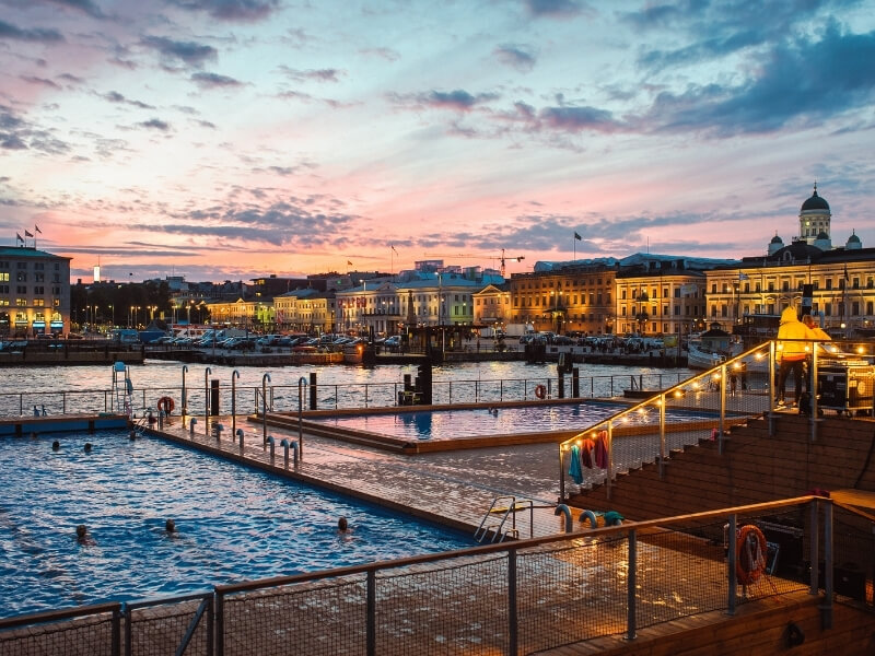 Helsinki's skyline at dusk with a pink and blue cloudy sky overhead. In the foreground is Allas Seapool, which several pools and traditional Finnish saunas in the heart of Helsinki. Photo Credit: Allas Seapool Helsinki Finland