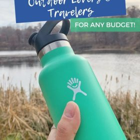 Text: Best Gifts Outdoor Lovers & Travelers for any budget! Image: Mint green water bottle is held up in front of a lake with tall yellow grass growing around it.