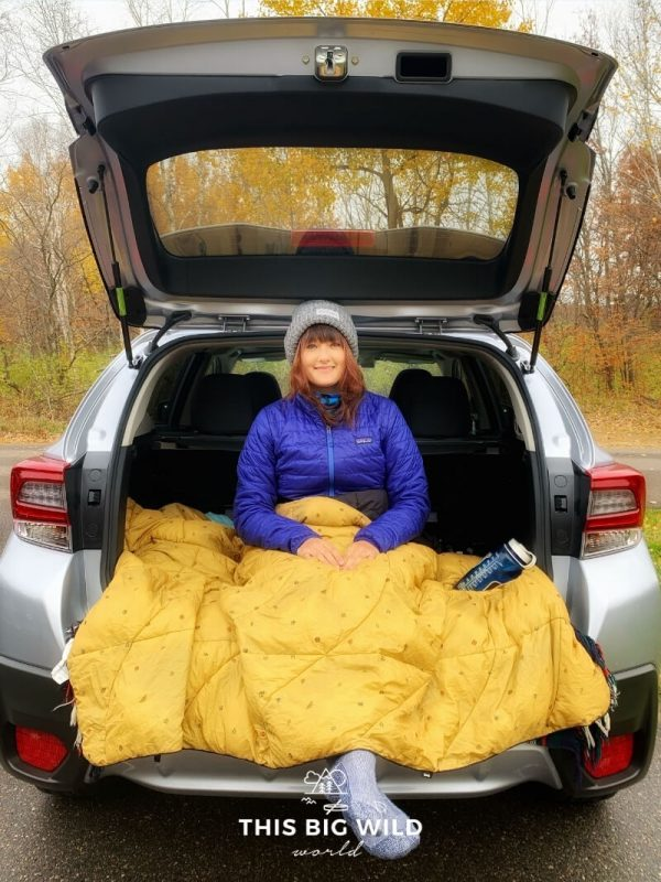 A woman sitting in the back of an SUV wearing a bright blue jacket, gray winter hat, blue wool socks covered in a yellow fluffy blanket. A blue water bottle sits on the blanket.