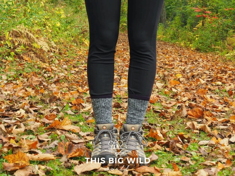 Close up of a woman's legs wearing balck leggings, black and white wool socks, and hiking boots standing in grass covered in bright red and orange leaves with grass in the background.