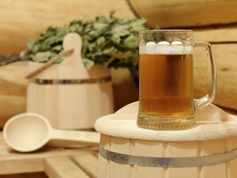 A glass of beer sits on top of a wooden barrel inside of a wood-lined sauna. In the background is a wooden bucket, spoon and birch leaves are resting on the sauna bench.