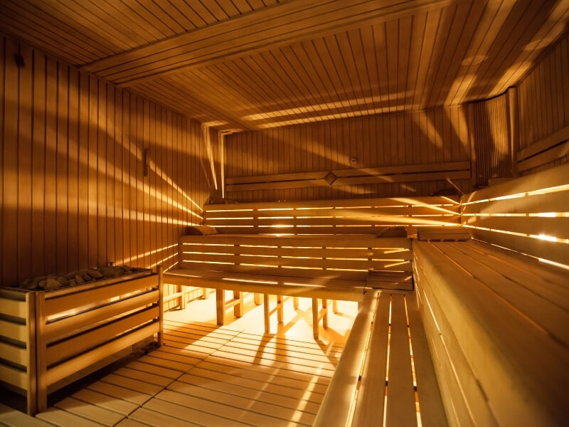 A dimly lit empty wooden sauna is brightened by rays of light coming in through the walls.