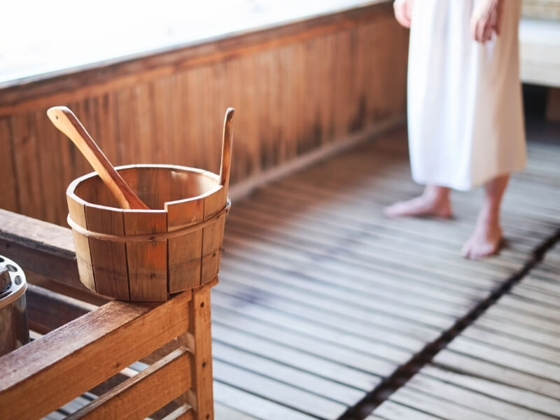 A wooden bucket with a wooden spoon rests on the edge of a railing next to the hot stones inside of a wooden sauna room.