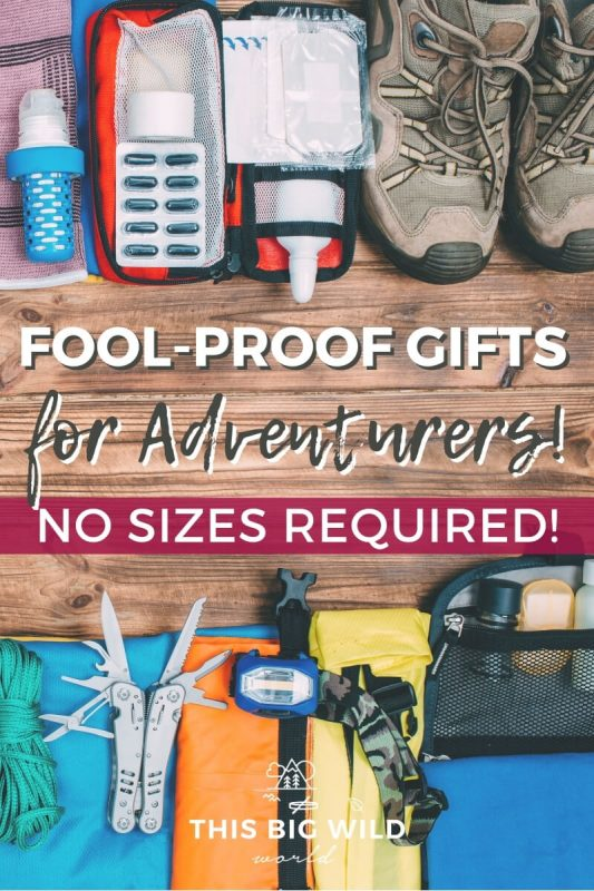 Text: Fool-proof gifts for Adventurers! No sizes required! Image: A flat lay of outdoor and travel items laid out on a wooden surface, including hiking shoes, a headlamp and a multi-tool.