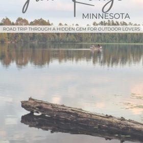 Text: Iron Range Minnesota - Road trip through a hidden gem for outdoor lovers Image: Two people in a canoe paddle away from the camera. A green treeline is in the distance and a log is resting in the water in the foreground.