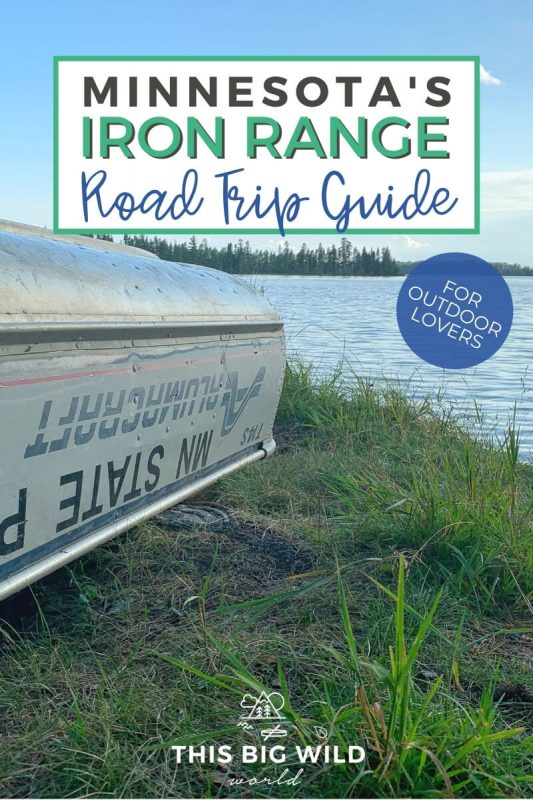 Text: Minnesota's Iron Range Road Trip Guide - for outdoor lovers Image: A metal canoe rests upside down along the shore of a lake in the grass.