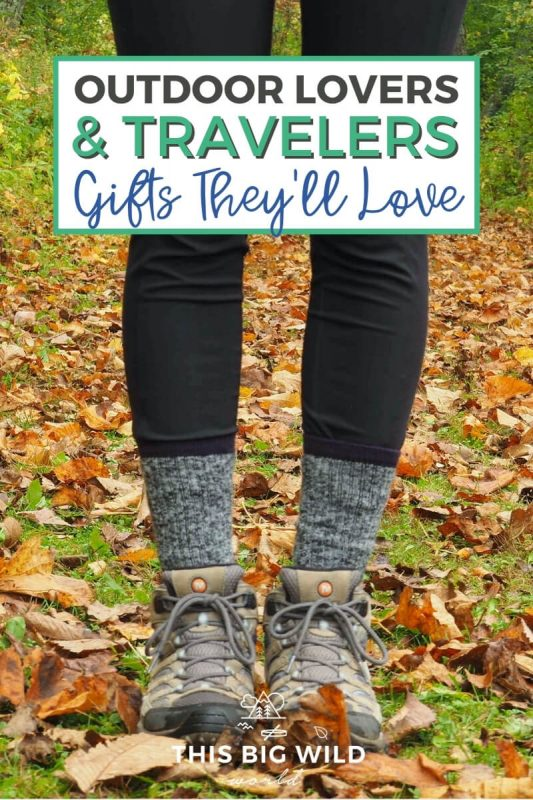 Text: Outdoor Lovers & Travelers - Gifts They'll Love Image: A woman with black leggings and black and white socks in hiking boots stands among fallen autumn leaves.