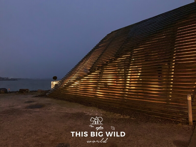 Loyly Sauna Helsinki Finland is located right on the sea and is made of horizontally placed wooden slats in an unique geometric shape. Light from inside of the sauna is visible from outside through the slats.