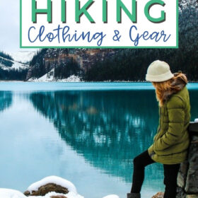 Text: Best winter hiking clothing and gear Image: Woman standing in snow leaning against a rock at the end of a calm blue lake. In the distance are snow covered mountains.