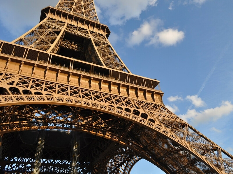 A partial view of the reddish metal structure of the Eiffel Tower in Paris France. Behind the Eiffel Tower is a bright blue sky with white fluffy clouds.