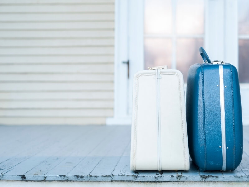 Two old-fashioned suitcases sit side by side on a wooden porch in front of a white house.