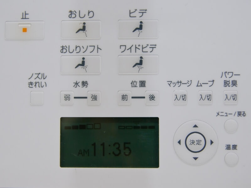 An up close view of the keypad on a Japanese bidet. There are several buttons with Japanese symbols and icons for spraying water and air as well as flushing the toilet.