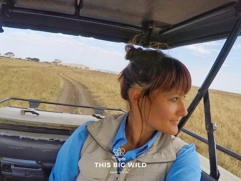 Me, a woman, with a messy bun looks to the right out of the frame. I am standing in a safari vehicle with the top raised and a dirt road with tall yellow grass behind us to the horizon.