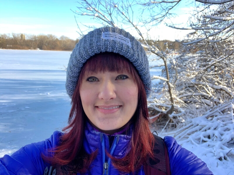 Me with red hair wearing a gray beanie and blue winter jacket hiking along a frozen snow-covered lake in Minneapolis, Minnesota.