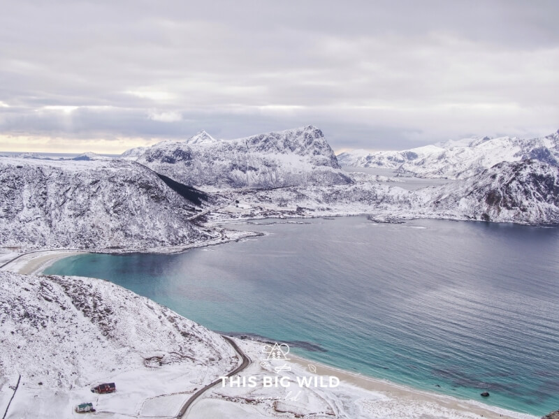 Snow covers the dark rock jutting out of the fjords in the Lofoten Islands in Norway. The water is bright blue as seen from above on the hike to Mt Mannen.