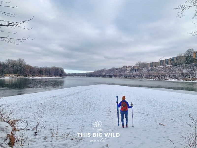 Me standing on a snow covered piece of land at the point where the Mississippi and Minnesota Rivers meet on Pike Island in Fort Snelling State Park in Minnesota.